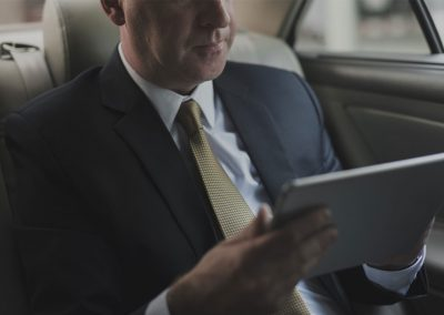 businessman-using-tablet-working-car-inside-PFDDYTA