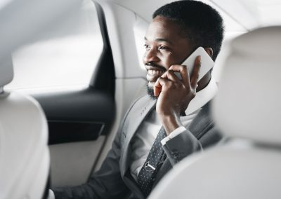 happy-afro-businessman-talking-on-cellphone-in-YRWS4DK